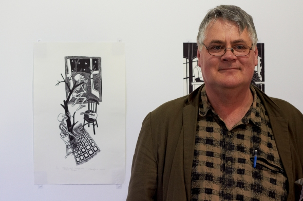 John Ryrie standing by his relief prints on exhibition