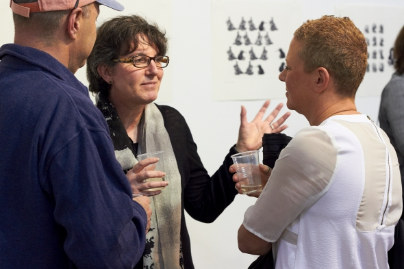 Solander Gallery NZ Director, Paulette Robinson, chatting in front of prints by Michael Kempson